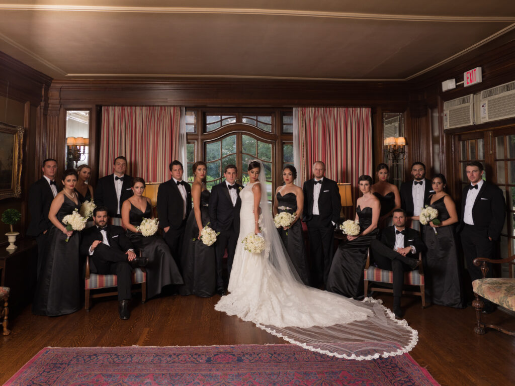 Group of people at a wedding. Bride is wearing a large veil and a wedding dress.