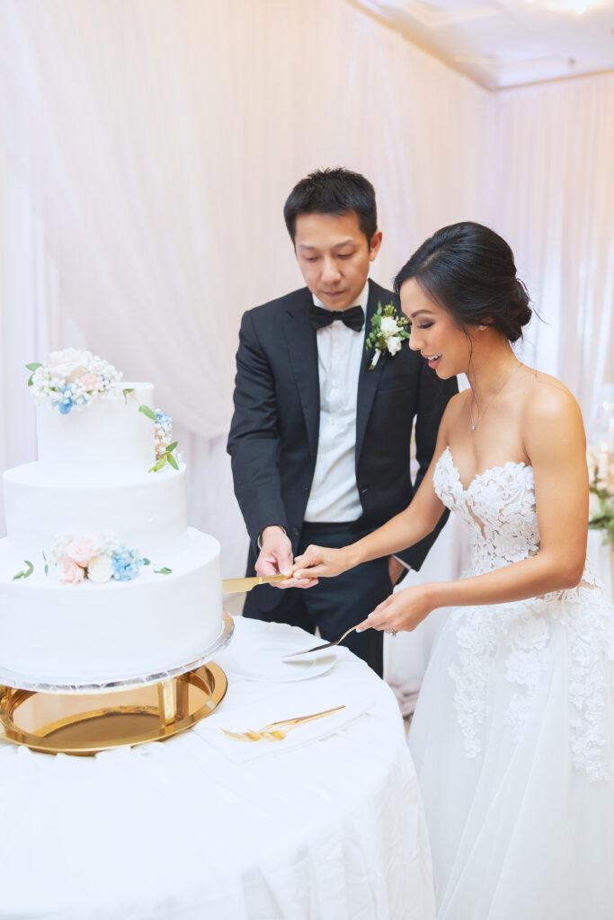 Husband and wife slicing a wedding cake